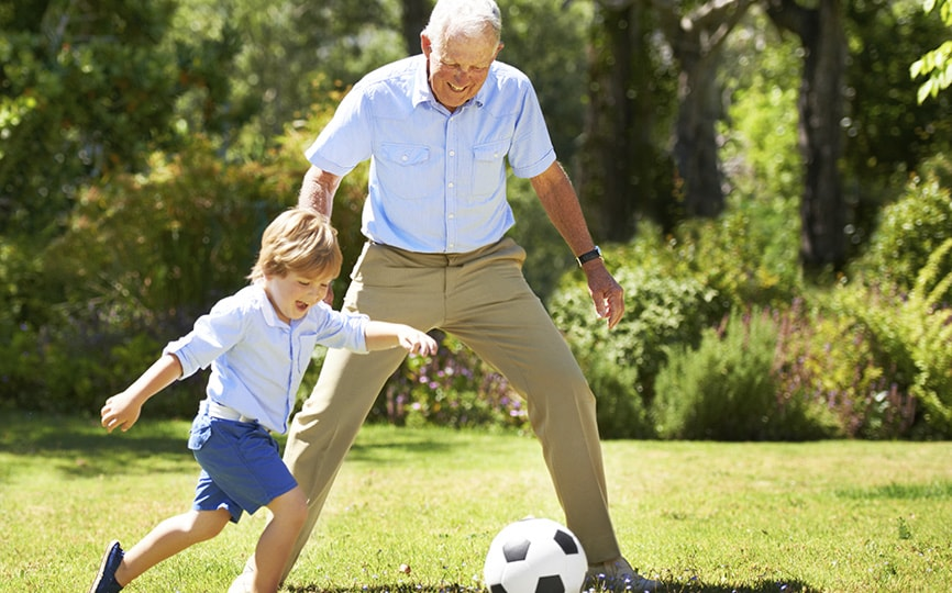 Elderly man playing soccer with boy