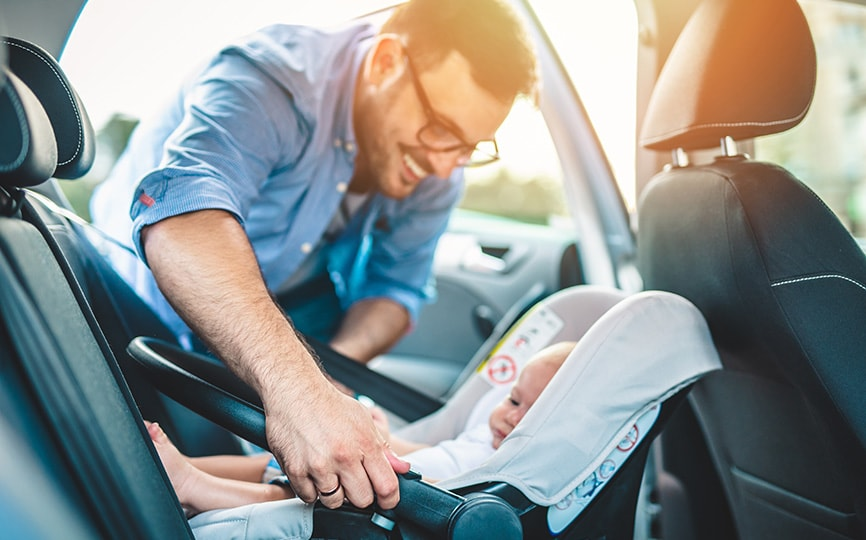 man putting baby into car seat