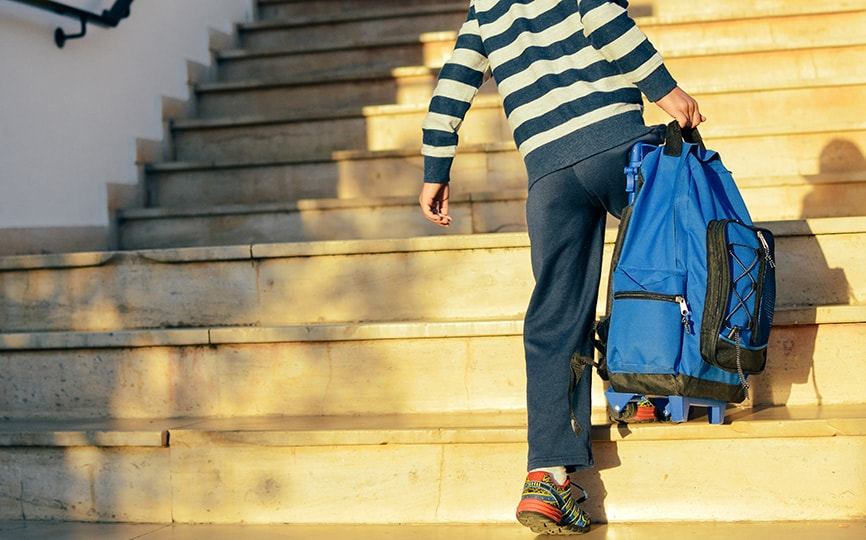 child carrying a heavy backpack up stairs