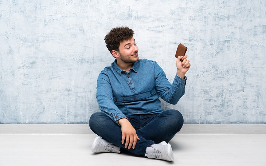 Man sitting down holding his wallet