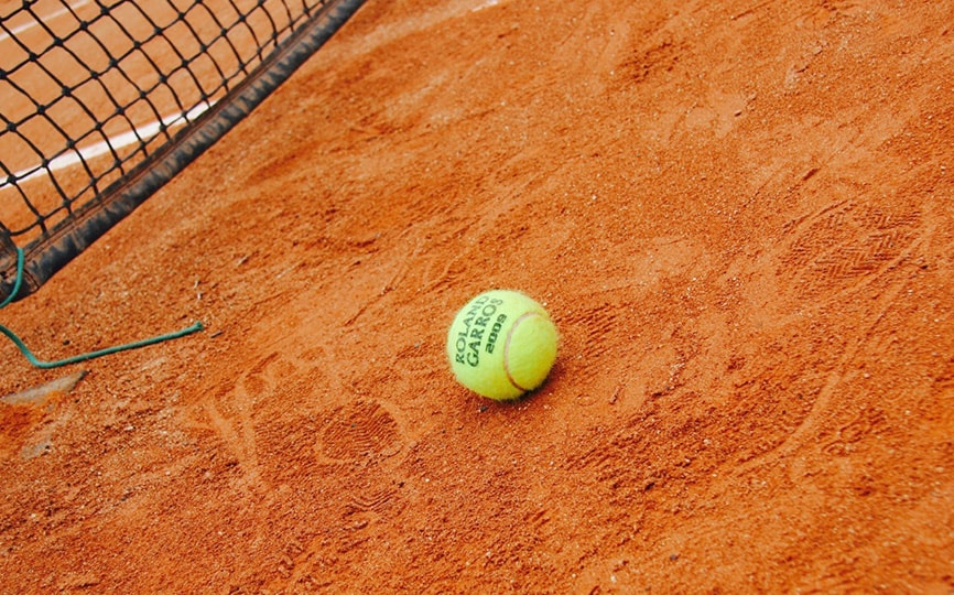 tennis ball lying on clay court